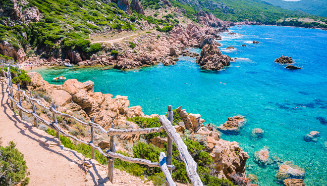 A walking track overlooking blue sea in Sardinia