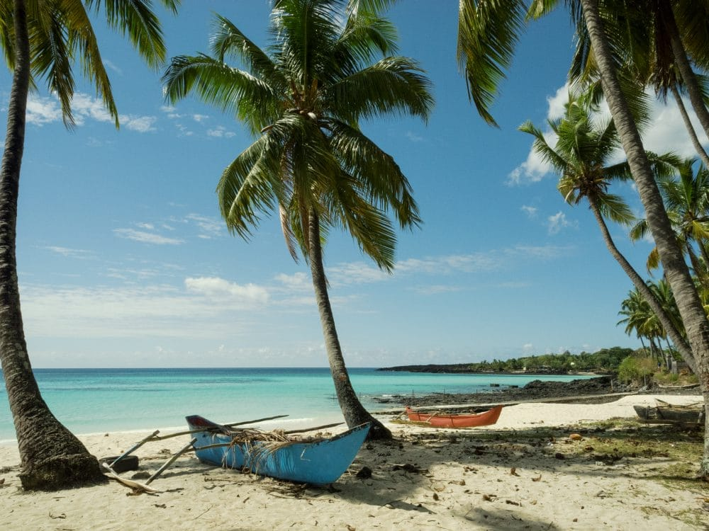 Empty white sand beach with two fishing boats on Comoros, a small island off the coast of Madagascar
