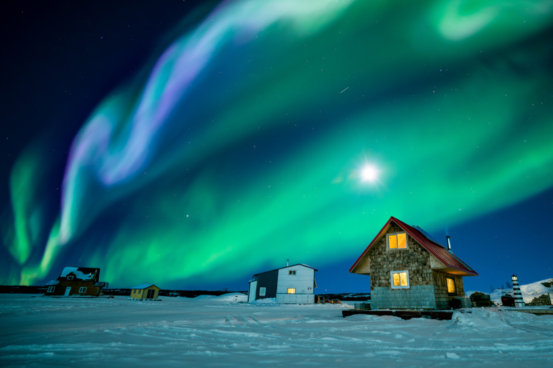 Aurora over small homes in Yellowknife