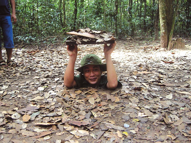 Local guide demonstrating the Cu Chi tunnels